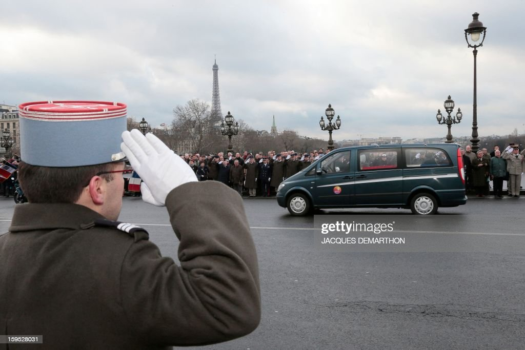 A French soldier stands at attention as the hearse carrying the coffin of French air force lieutenant Damien Boiteux, killed on January 11, 2013 during French military operation 'Serval' in Mali, crosses the Alexandre III bridge in Paris, on January 15, 2013. French pilot Damien Boiteux was killed during a helicopter raid launched to support Mali ground troops in the battle for the key town of Kona, and to prevent Islamist groups controlling northern Mali from advancing toward the capital Bamako. AFP PHOTO JACQUES DEMARTHON