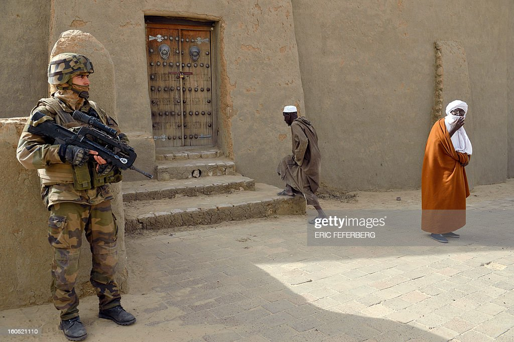 A French soldier (L) stands guard in front of the Djingareyber mosque as the imam of the mosque (R) arrives on January 31, 2013 in Timbuktu. France's President will visit the 700-year-old mudtimbuktu mosque of Djingareyber during his one day visit in Mali.
