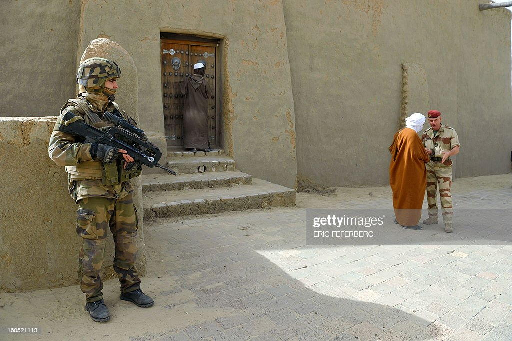 A French soldier (L) stands guard in front of the Djingareyber mosque as the imam of the mosque (R) speaks with a French military chaplain on January 31, 2013 in Timbuktu. France's President will visit the 700-year-old mudtimbuktu mosque of Djingareyber during his one day visit in Mali.