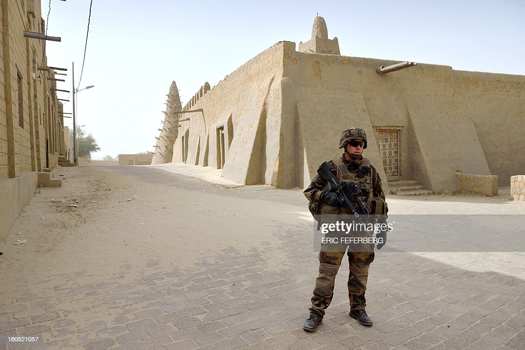 A French soldier stands guard in front of the Djingareyber mosque on February 2, 2013 in Timbuktu. France's President will visit the 700-year-old mudtimbuktu mosque of Djingareyber during his one day visit in Mali.