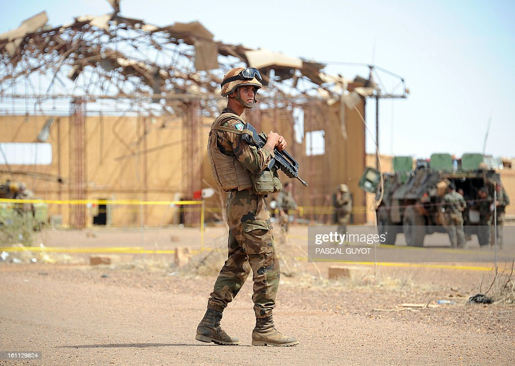 A French soldier stands guard while French army deminers secure a hangar at the airport in the Malian northern city of Gao, on February 9, 2013. Two Malian soldiers and four civilians have already been killed by landmines, and French troops are still fighting off what Paris called 'residual jihadists' in reclaimed territory. AFP PHOTO / PASCAL GUYOT