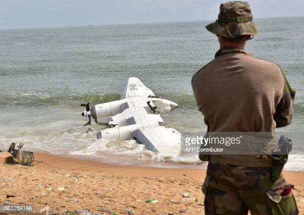 A French soldier stands on the beach of PortBouet in Abidjan near the wreckage of a cargo plane that crashed off Ivory Coast killing four on October...