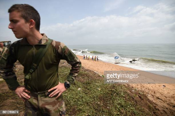A French soldier stands on the beach of PortBouet in Abidjan on October 14 2017 as rescuers try to pull out the wreckage of a cargo plane that...
