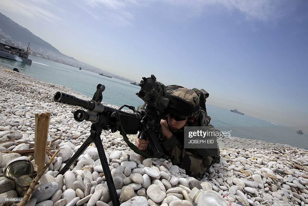A French soldier takes a position as he takes part in sea and land war games with the Lebanese Army at the bay of Jounieh, north of Beirut, on March 26, 2013.