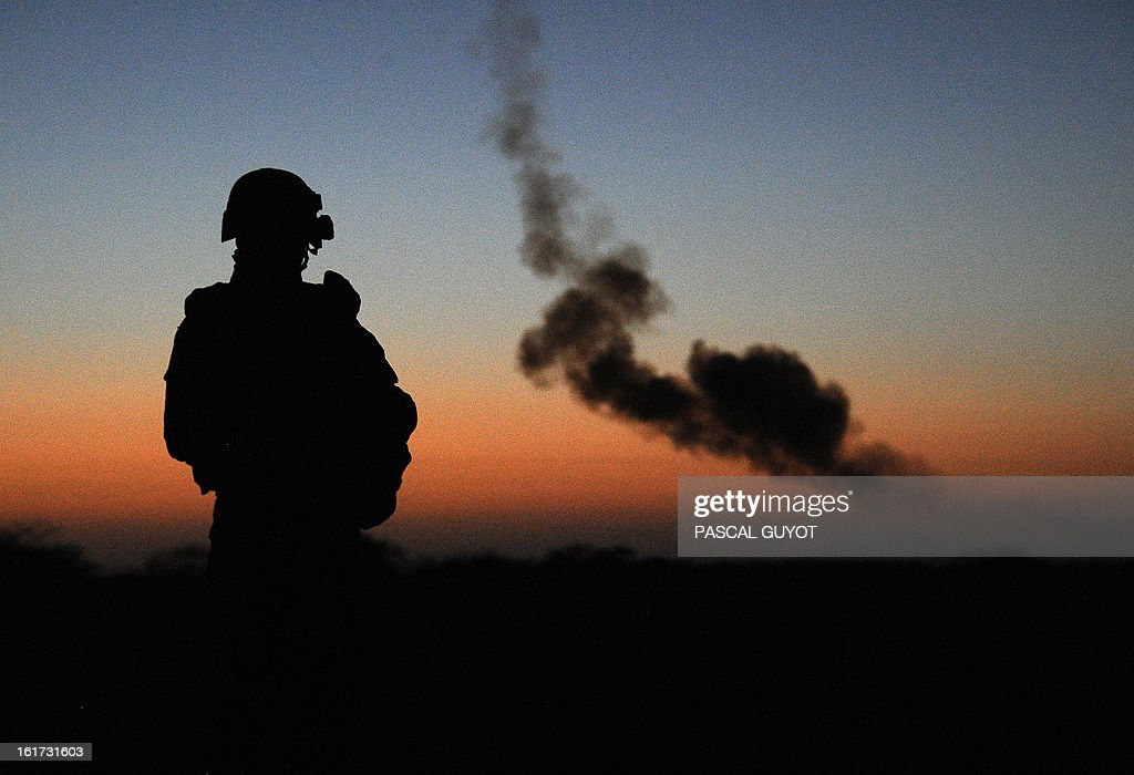 A French soldier watches a controlled explosion of an artisanal bomb and other munitions by a bomb-disposal expert on February 14, 2013 found by the French army in Gao, in northern Mali.