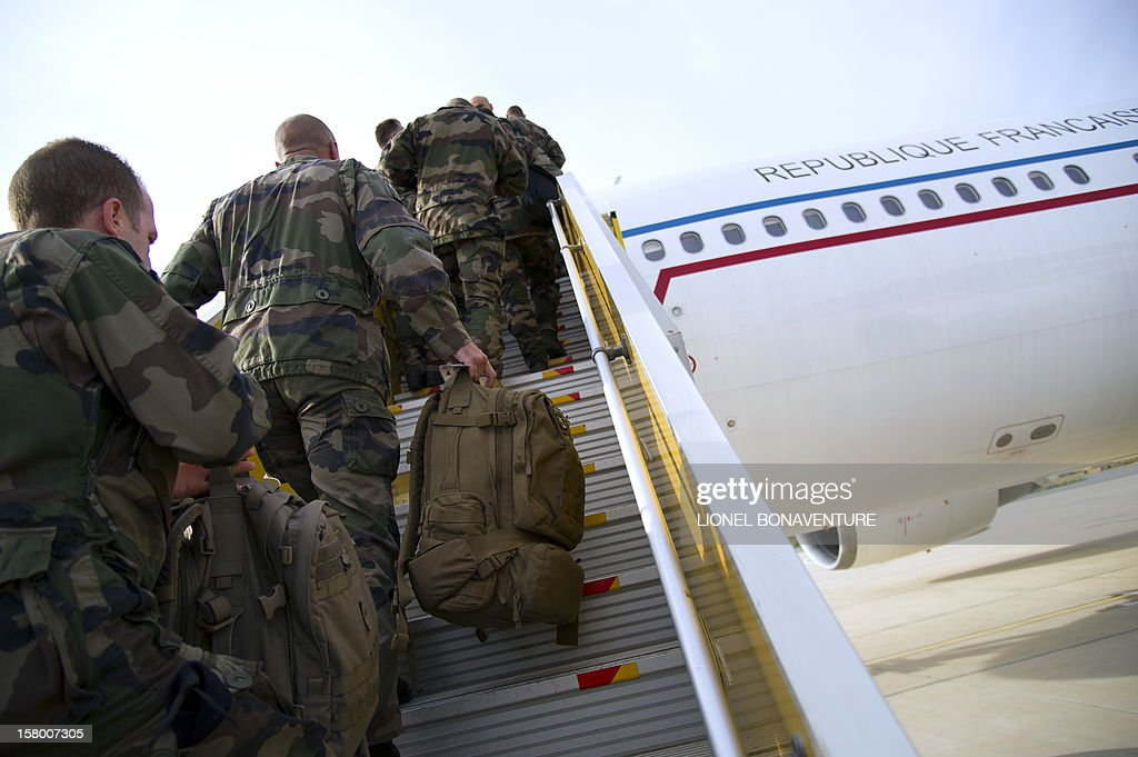 French soldiers board a plane at Paphos airport in Cyprus in December 8, 2012 before leaving for France. French Defence Minister, Jean-Yves Le Drian today welcomed some 150 French soldiers returning from Afghanistan. AFP PHOTO / LIONEL BONAVENTURE