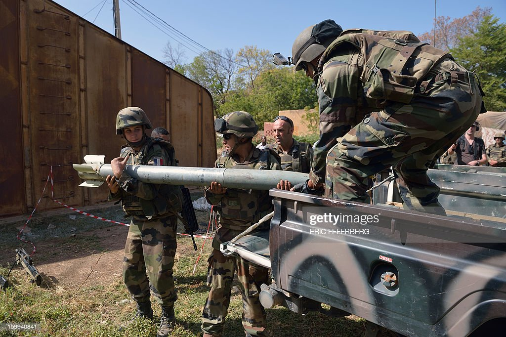 French soldiers carry carefully a rocket they found with a stock of munitions in Diabali (400km north of Bamako) on January 23, 2013. The French destroyed all the munitions that belonged to the islamists to secure the town.