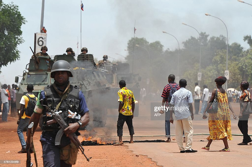French soldiers from Sangaris operation patrol as students demonstrate on March 12, 2014 in Bangui, to ask for the payment of their arrears of scholarships. The rapid spiral of inter-religious violence in Centrafrica led France to deploy troops in its chronically unstable former colony to back an African Union force already on the ground. KAMBOU