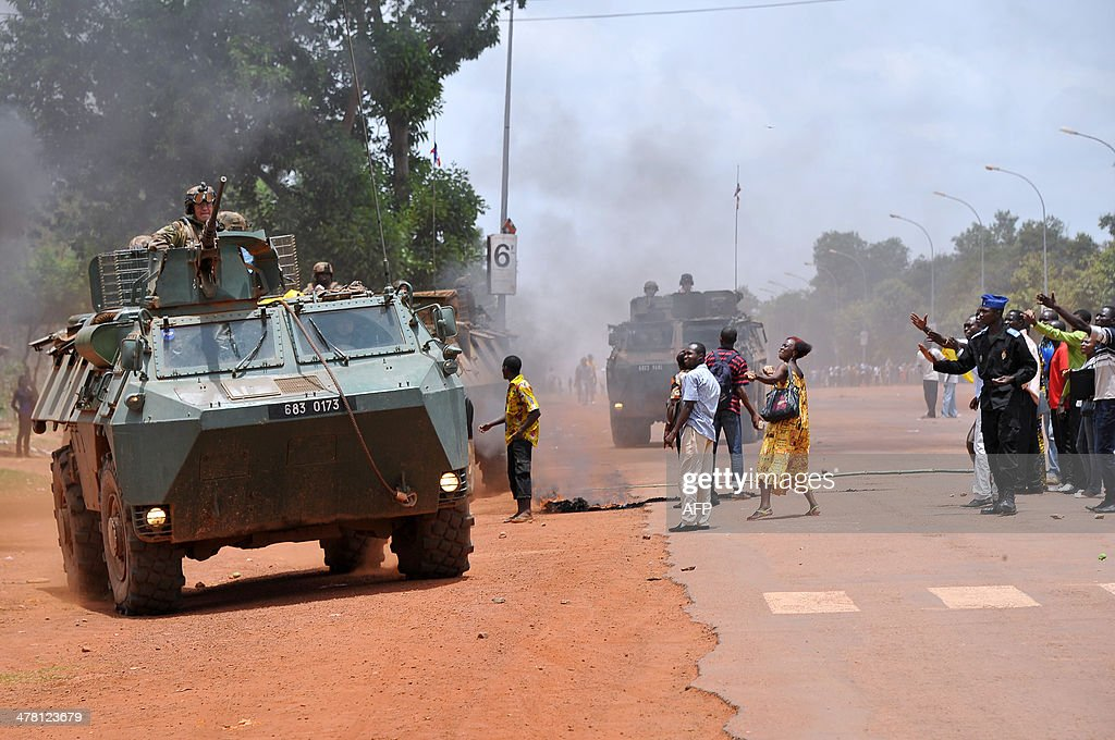 French soldiers from Sangaris operation patrol in armoured vehicles as a member of Centrafrican Gendarmerie stands at right near the Bangui university where students demonstrate on March 12, 2014, to ask for the payment of their arrears of scholarships. The rapid spiral of inter-religious violence in Centrafrica led France to deploy troops in its chronically unstable former colony to back an African Union force already on the ground. KAMBOU