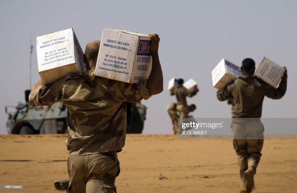 French soldiers from the 126th Regiment Infantery carry boxes containing water bottles on April 8, 2013 some 105 kilometers North of Gao. A French force of 1,000 soldiers in a major offensive has swept a valley thought to be a logistics base for Al-Qaeda-linked Islamists near the Malian city of Gao. Operation Gustav, one of France's largest actions since its intervention against insurgents in January, will involve dozens of tanks, helicopters, drones and airplanes, said General Bernard Barrera, commander of the French land forces in Mali. France is to start withdrawing its 4,000 troops from Mali at the end of April, and plans to leave a 'support force' of 1,000 soldiers after elections promised for July. AFP PHOTO / JOEL SAGET