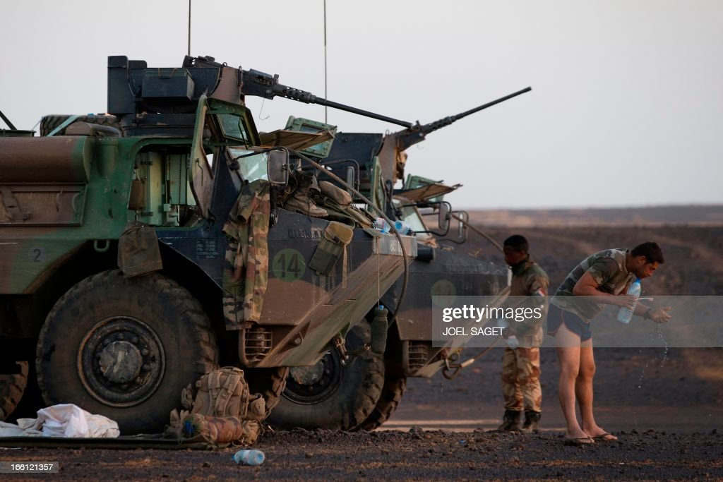 French soldiers from the 126th Regiment Infantery cleans his teeth near an armoured personnel carrier (VAB) early in the morning on April 8, 2013 some 105 kilometers North of Gao