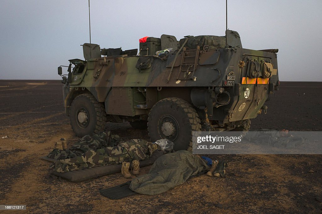 French soldiers from the 126th Regiment Infantery sleep near an armoured personnel carrier (VAB) early in the morning on April 8, 2013 some 105 kilometers North of Gao. A French force of 1,000 soldiers in a major offensive has swept a valley thought to be a logistics base for Al-Qaeda-linked Islamists near the Malian city of Gao. Operation Gustav, one of France's largest actions since its intervention against insurgents in January, will involve dozens of tanks, helicopters, drones and airplanes, said General Bernard Barrera, commander of the French land forces in Mali. AFP PHOTO / JOEL SAGET