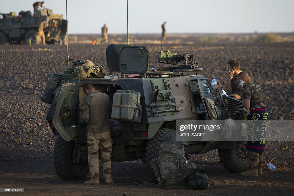 French soldiers from the 126th Regiment Infantery stand near an armoured personnel carrier (VAB) early in the morning on April 8, 2013 some 105 kilometers North of Gao. A French force of 1,000 soldiers in a major offensive has swept a valley thought to be a logistics base for Al-Qaeda-linked Islamists near the Malian city of Gao. Operation Gustav, one of France's largest actions since its intervention against insurgents in January, will involve dozens of tanks, helicopters, drones and airplanes, said General Bernard Barrera, commander of the French land forces in Mali. AFP PHOTO / JOEL SAGET