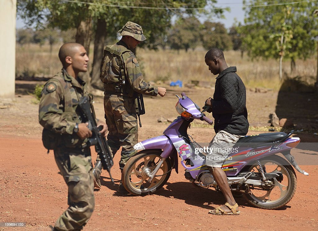 French soldiers from the 21st Rima check the identity of a Malian man driving a motorcycle near the Malian army 101 airbase, where the French troops are stationed, on January 18, 2013, near Bamako. France now has 1,800 troops on the ground in Mali, inching closer to the goal of 2,500 it plans to deploy in its African former colony, Defence Minister Jean-Yves Le Drian said today. That was 400 more than a day earlier, said the minister as he met with French special forces in the western port of Lorient. The troops have been sent to help the Malian army regain control of the north from Islamist groups. AFP PHOTO / ERIC FEFERBERG