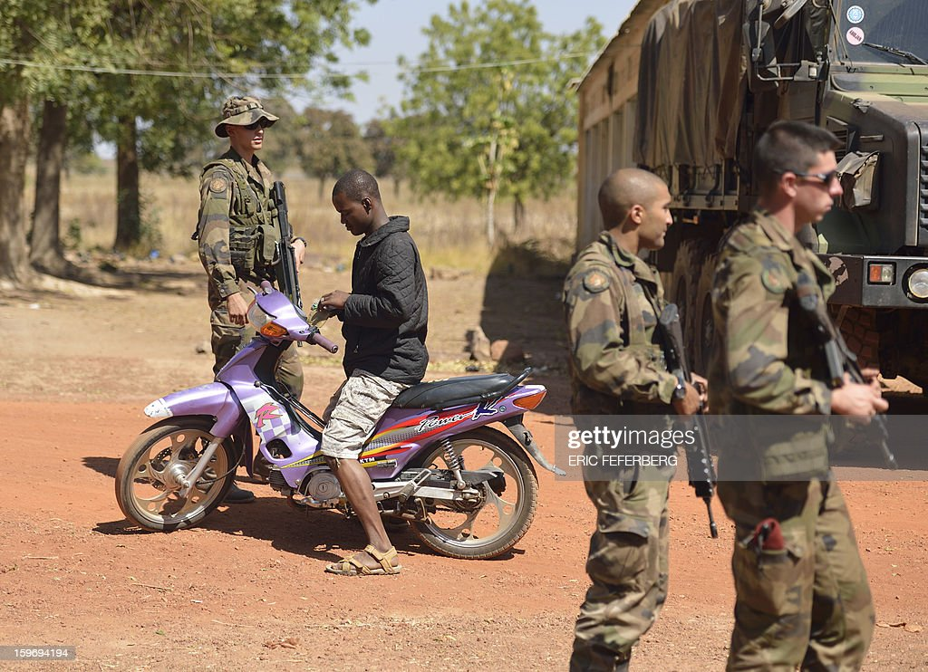 French soldiers from the 21st Rima check the identity of a Malian man driving a motorcycle near the Malian army 101 airbase, where the French troops are stationed, on January 18, 2013, near Bamako. France now has 1,800 troops on the ground in Mali, inching closer to the goal of 2,500 it plans to deploy in its African former colony, Defence Minister Jean-Yves Le Drian said today. That was 400 more than a day earlier, said the minister as he met with French special forces in the western port of Lorient. The troops have been sent to help the Malian army regain control of the north from Islamist groups.