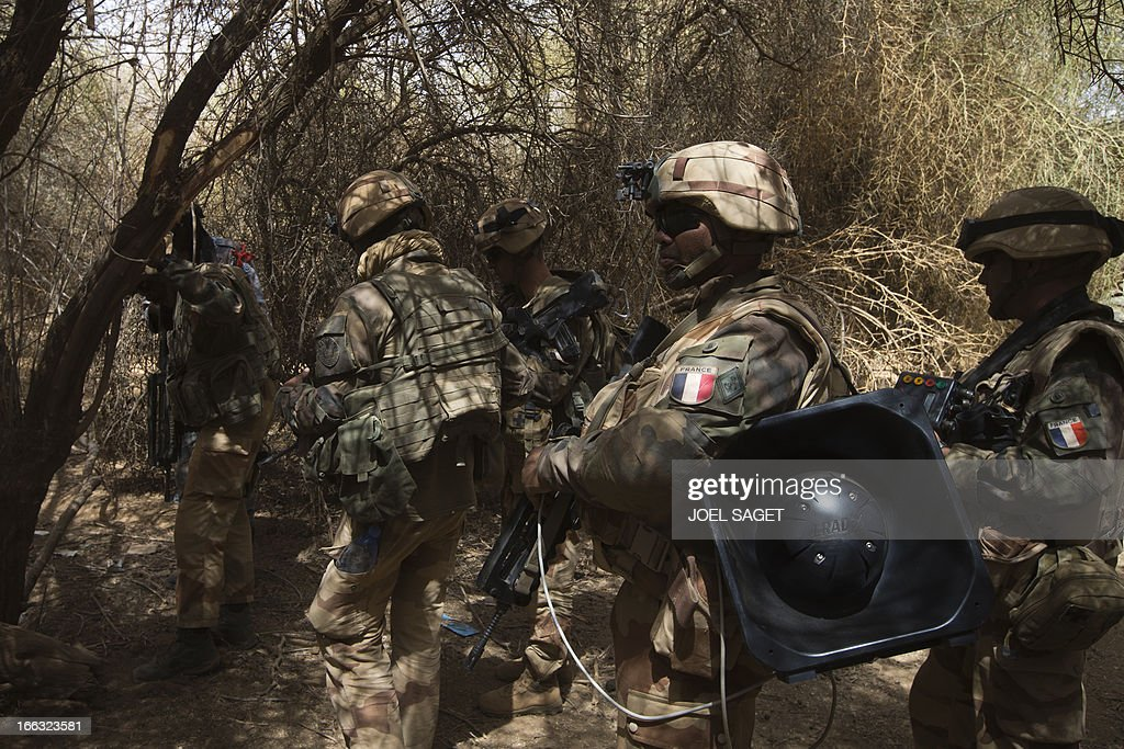French soldiers from the 92 RI (Infantry Regiment) walk with a loud speaker used to speak to the population on April 10, 2013, 105 kms north of the northeastern Malian city of Gao, in day three of Operation Gustav, a hunt for Islamist fighters in a valley in northern Mali and one of France's largest military operations during its three-month intervention in its former colony. Operation Gustav comes with France preparing to withdraw three-quarters of the 4,000 troops it deployed in January to block a feared advance on the Malian capital Bamako by Al Qaeda-linked insurgents.