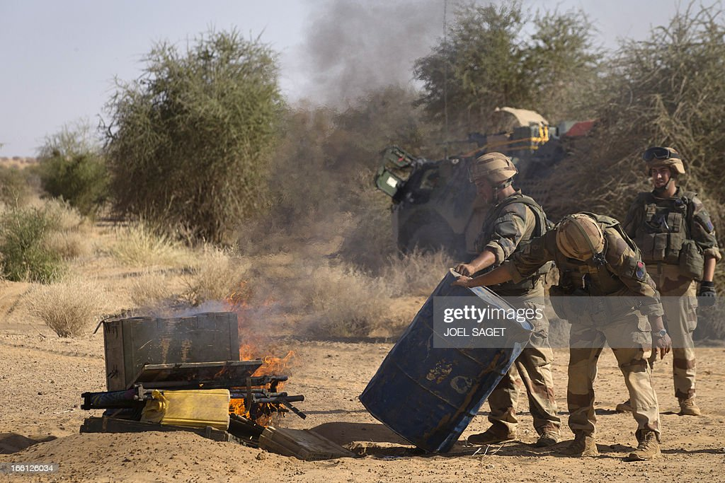 French soldiers from the 92nd Regiment Infantery burn items allegedly belonging to Mujao forces on April 8, 2013 during a military operation some 105 kilometers North of Gao. A French force of 1,000 soldiers in a major offensive has swept a valley thought to be a logistics base for Al-Qaeda-linked Islamists near the Malian city of Gao. Operation Gustav, one of France's largest actions since its intervention against insurgents in January, will involve dozens of tanks, helicopters, drones and airplanes, said General Bernard Barrera, commander of the French land forces in Mali. France is to start withdrawing its 4,000 troops from Mali at the end of April, and plans to leave a 'support force' of 1,000 soldiers after elections promised for July. AFP PHOTO / JOEL SAGET