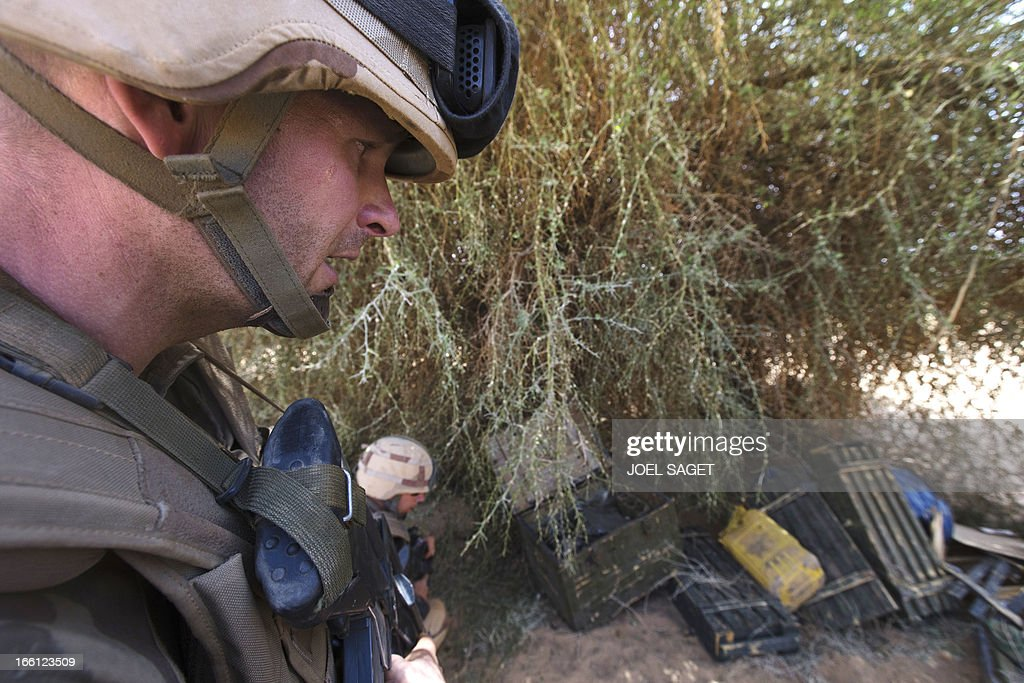 French soldiers from the 92nd Regiment Infantery stand near ammunition allegedly belonging to Mujao forces as they take part in a military operation on April 8, 2013 some 105 kilometers North of Gao. A French force of 1,000 soldiers in a major offensive has swept a valley thought to be a logistics base for Al-Qaeda-linked Islamists near the Malian city of Gao. Operation Gustav, one of France's largest actions since its intervention against insurgents in January, will involve dozens of tanks, helicopters, drones and airplanes, said General Bernard Barrera, commander of the French land forces in Mali. France is to start withdrawing its 4,000 troops from Mali at the end of April, and plans to leave a 'support force' of 1,000 soldiers after elections promised for July. AFP PHOTO / JOEL SAGET