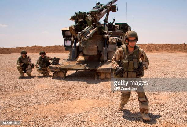 French soldiers from the Wagram Task Force stand next to a unit of CAESAR a French selfpropelled 155 mm howitzer north of Mosul on July 13 as the...