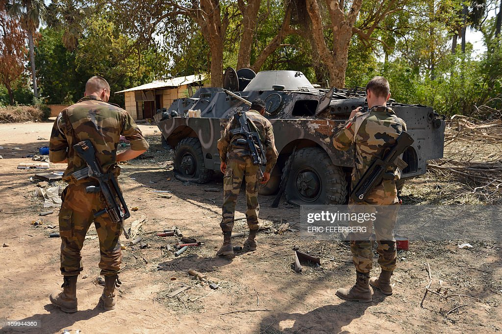French soldiers inspect a Malian armoured vehicle on January 23, 2013 in the Malian barracks that was occupied by Islamists in Diabaly (400km north of the capital Bamako), before a French air strike destroyed it. French soldiers destroyed the munitions that belonged to the Islamists to secure the town. AFP PHOTO / ERIC FEFERBERG
