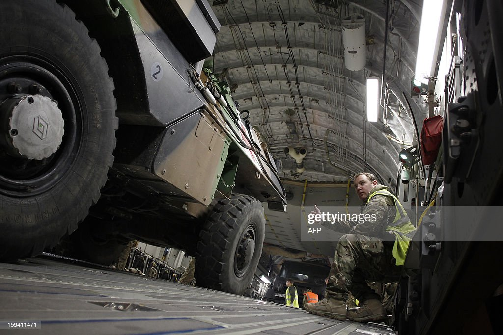 French soldiers load a armoured vehicle in a British army Boeing C-17 cargo aircraft arriving from British Brize Norton base en route to Bamako, on January 13, 2013 at the Evreux military Base. Britain supports France's decision to send troops to support an offensive by Mali government forces against Islamist rebels. AFP PHOTO CHARLY TRIBALLEAU