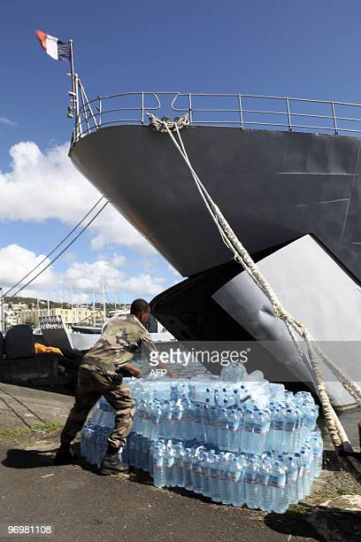 French soldiers load packs of water on January 15 2010 aboard the Francis Garnier military ship in FortdeFrance in the Caribbean island of Martinique...