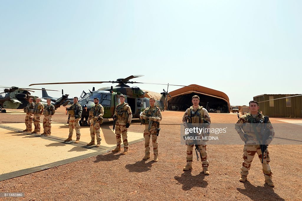 French soldiers of Barkhane counterterrorism operation in Africa's Sahel region attend in front of their Caiman war helicopter the visit of France...