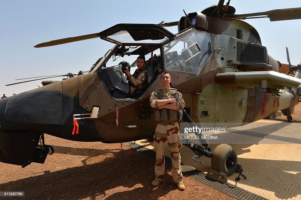 French soldiers of Barkhane counterterrorism operation in Africa's Sahel region are pictured next to their war helicopter before the visit of France...
