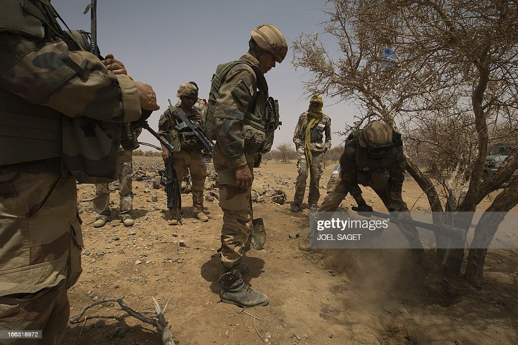 French soldiers of the 92nd Infantery Regiment look for dig a hole in the ground on April 10, 2013, 105 kms north of the northeastern Malian city of Gao, in day three of Operation Gustav, a hunt for Islamist fighters in a valley in northern Mali and one of France's largest military operations during its three-month intervention in its former colony. Operation Gustav comes with France preparing to withdraw three-quarters of the 4,000 troops it deployed in January to block a feared advance on the Malian capital Bamako by Al Qaeda-linked insurgents. AFP PHOTO / JOEL SAGET
