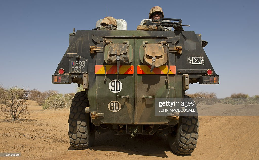 French soldiers of the 92nd Infantry Regiment (92eme R.I) keep watch in an armoured personnel carrier (VAB) as a military convoy makes its way to the village of Amakouladji north of Gao on March 10, 2013, to assess the needs of the local population there.