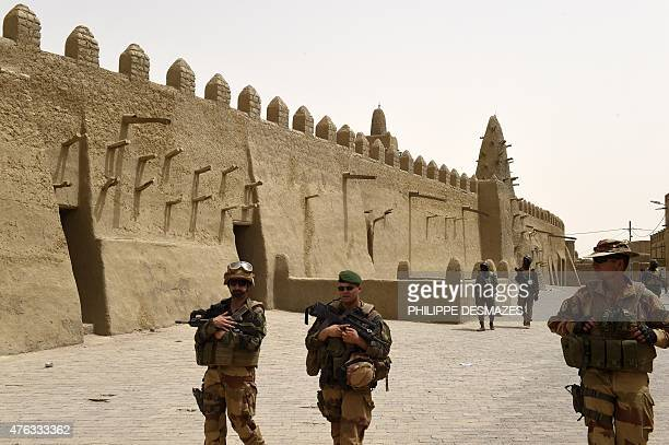 French soldiers of the 93rd Mountain Artillery Regiment and soldiers of the Malian Armed Forces patrol next to the Djingareyber Mosque on June 6 2015...