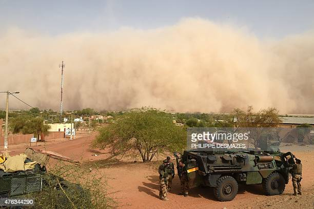 French soldiers of the French 93rd Mountain Artillery Regiment wait while a sand storm is coming on June 3 2015 in Goundam in the Timbuktu region...