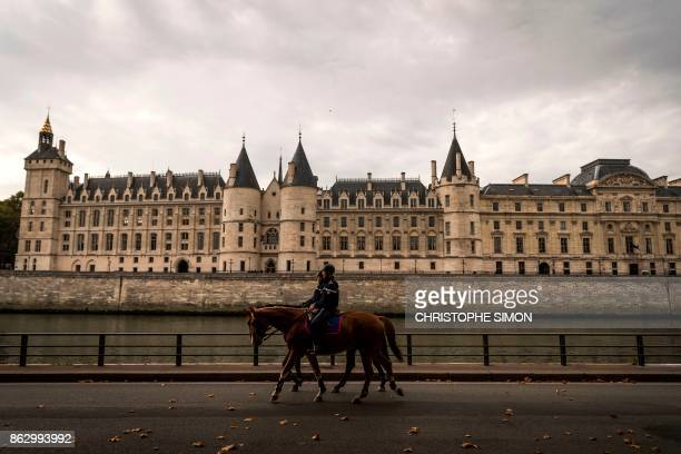 TOPSHOT French soldiers of the gendarmerie riding horses patrol along the river Seine banks next to the Conciergerie historic building in Paris on...