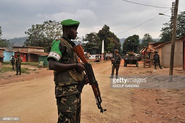 French soldiers of the Sangaris operation and Rwandese MISCA peacekeepers stand guard at the entrance of Kasai military camp after exSeleka...