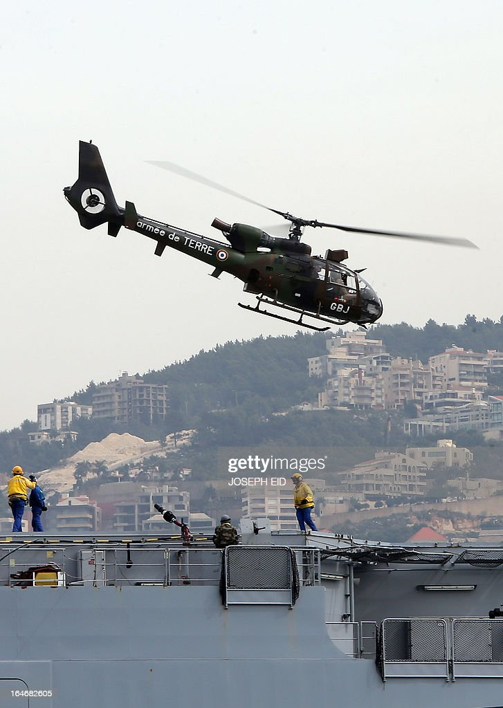 French soldiers on board a BPC Tonnerre assault helicopter carrier prepare helicopters as they take part in sea and land war games with the Lebanese Army at the bay of Jounieh, north of Beirut, on March 26, 2013.