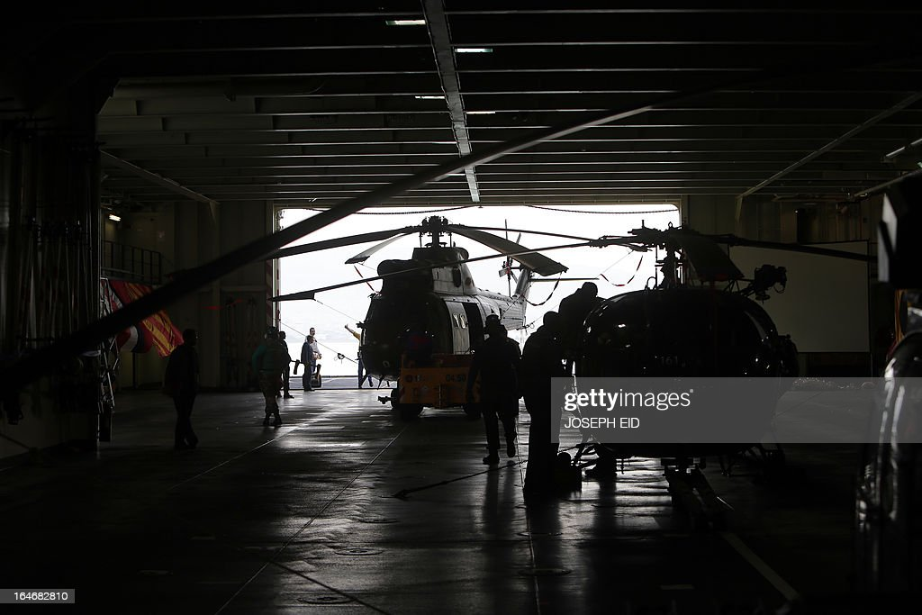 French soldiers on board a BPC Tonnerre assault helicopter carrier prepare helicopters as they take part in sea and land war games with the Lebanese forces at the bay of Jounieh, north of Beirut, on March 26, 2013.