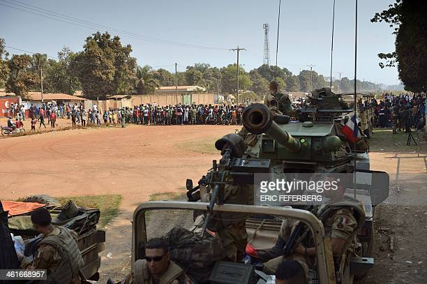 French soldiers part of the Sangaris operation hold their position on January 10 2014 at the entrance of Bangui Mpoko airport as displaced people...
