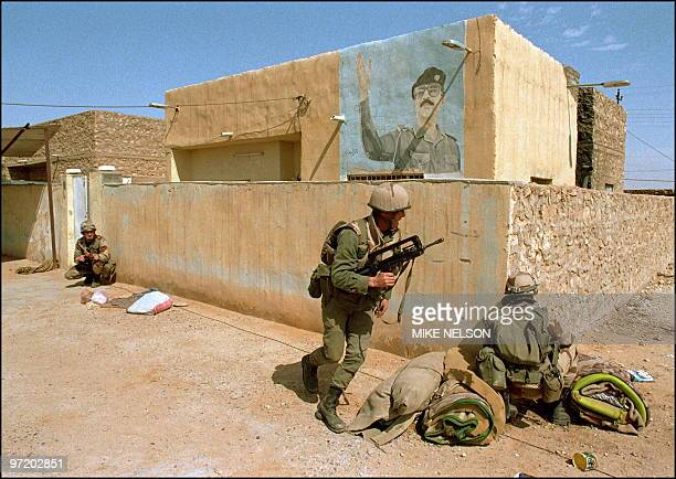 French soldiers patrol 27 February 1991 next to a mural of Iraqi President Saddam Hussein in the town of Salman far inside southern Iraq Iraq's...