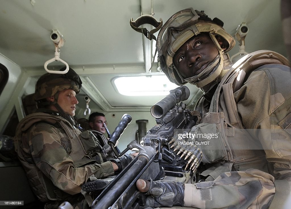 French soldiers patrol aboard an armoured vehicle near the central police station on February 11, 2013 in Gao, one day after Islamist gunmen battled French and Malian troops. A French attack helicopter destroyed the central police station in Gao in a pre-dawn assault, after rebels from the Movement for Oneness and Jihad in West Africa (MUJAO) hiding in the building opened fire on Malian troops Sunday, sparking an hours-long street battle.