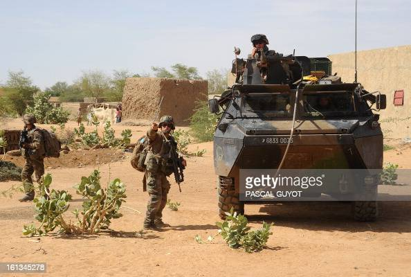 French soldiers patrol at the site where a suicide bomber blew himself up on February 10 2013 in northern Gao on the road to GouremFighting between...