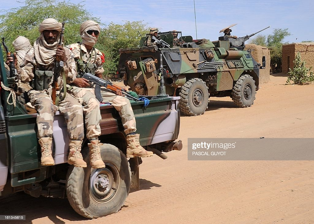 French soldiers (Background-R) patrol at the site where the suicide bomber blew himself up on February 10, 2013 in northern Gao on the road to Gourem. Fighting between Islamists rebels and Malian soldiers broke out in the center of Gao, the largest city in northern Mali, recently taken over by the French military and Malian armed Islamist groups, hit by two suicide bombings in two days. AFP PHOTO / PASCAL GUYOT