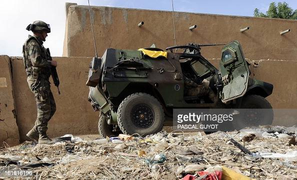 French soldiers patrol near the abandoned house where they found and defused a homemade bomb containing 600 kilos of explosives on February 13 2013...