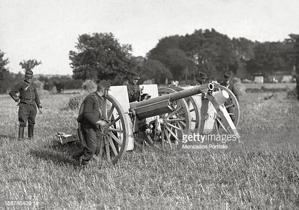 French soldiers positioning two cannons in a field during World War I 1910s