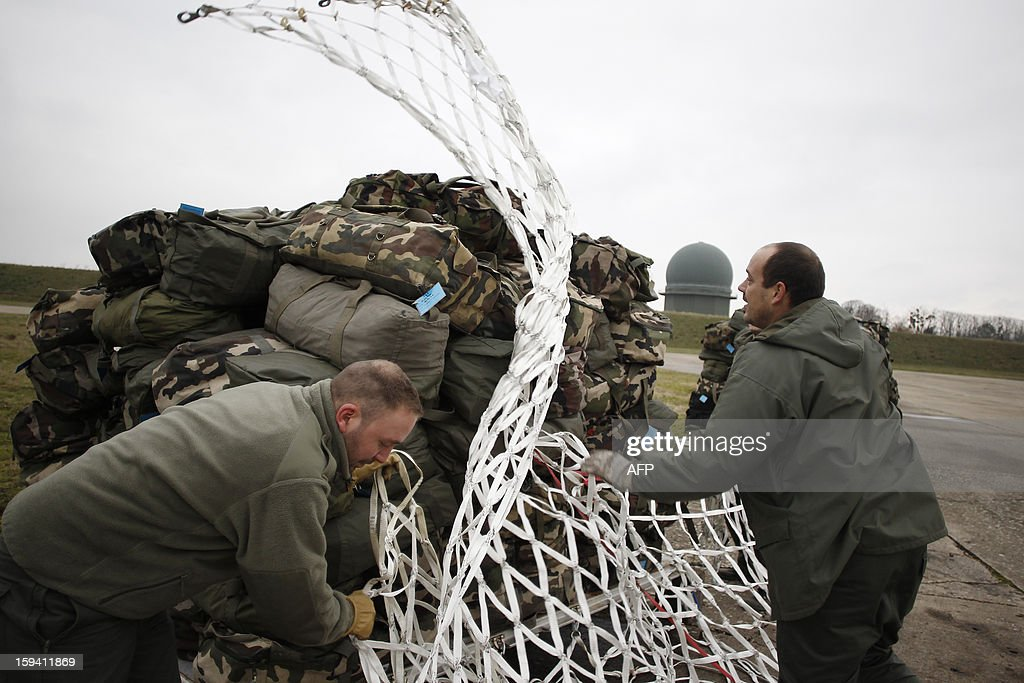 French soldiers prepare material to be load in a British army Boeing C-17 cargo aircraft arriving from British Brize Norton base en route to Bamako, on January 13, 2013 at the Evreux military Base. Britain supports France's decision to send troops to support an offensive by Mali government forces against Islamist rebels.