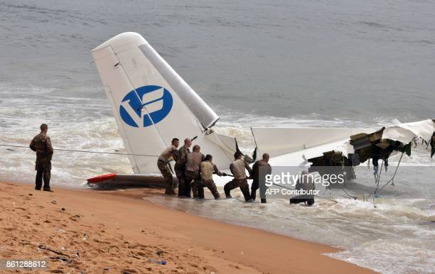 French soldiers pull out the wreckage of a cargo plane that crashed off Ivory Coast killing four on the beach of PortBouet in Abidjan on October 14...