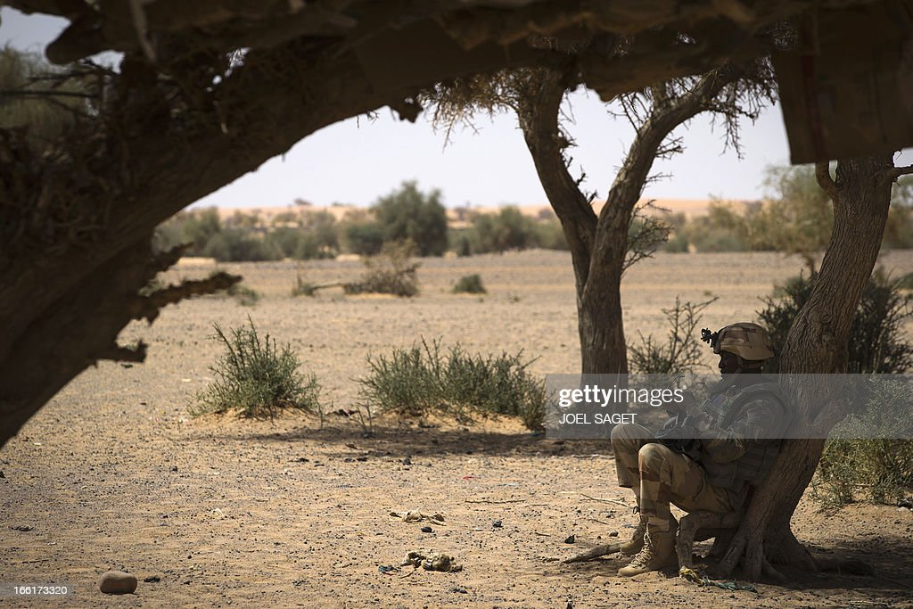 A French soldiers rests during the Operation Gustav, a hunt for Islamist fighters in a valley in northern Mali and one of France's largest military operations during its three-month intervention in its former colony, on April 9, 2013, 105 km North of Gao. Operation Gustav comes with France preparing to withdraw three-quarters of the 4,000 troops it deployed in January to block a feared advance on the Malian capital Bamako by Al Qaeda-linked insurgents. AFP PHOTO / JOEL SAGET