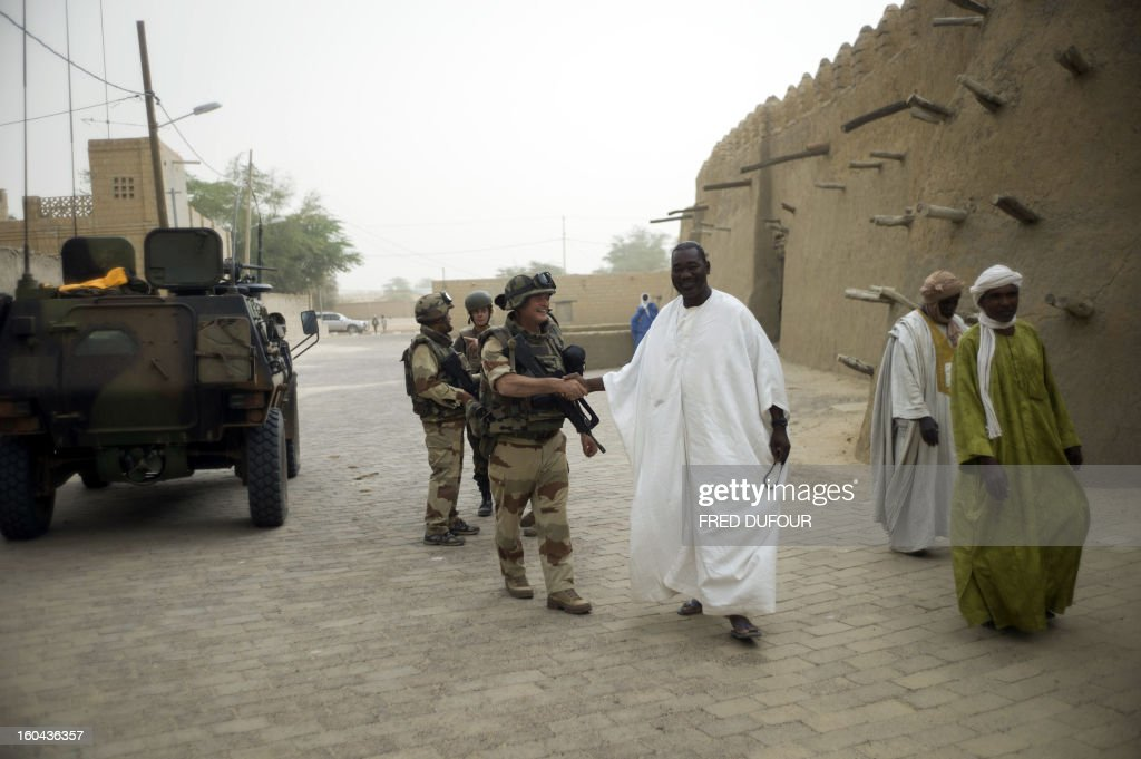 French soldiers salute Malian people after the prayer next to the Djingareyber mosque, on January 31, 2013 in Timbuktu. The fabled desert city of Timbuktu, an ancient centre of Islamic learning, has been recaptured on January 28 by French-led forces in their offensive against Islamist rebels who have been occupying Mali's north since last April. The extremists last year smashed up mausoleums of ancient saints and the entrance to the 15th-century Sidi Yahya mosque, claiming the sites were blasphemous. Reports had emerged in recent days that rebels fleeing the advancing soldiers had torched a building housing thousands of priceless manuscripts, but an expert said on January 30 that most had been smuggled to safety as the Islamists overran the city last year.