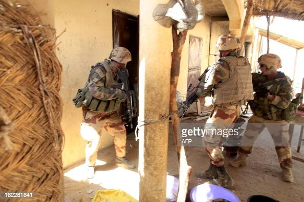 French soldiers search houses after clashes erupted in the city of Gao on February 21 2013 and an apparent car bomb struck near a camp housing French...