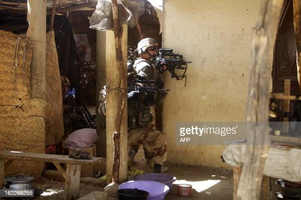 French soldiers search houses while clashes erupted in the city of Gao on February 21 2013 and an apparent car bomb struck near a camp housing French...