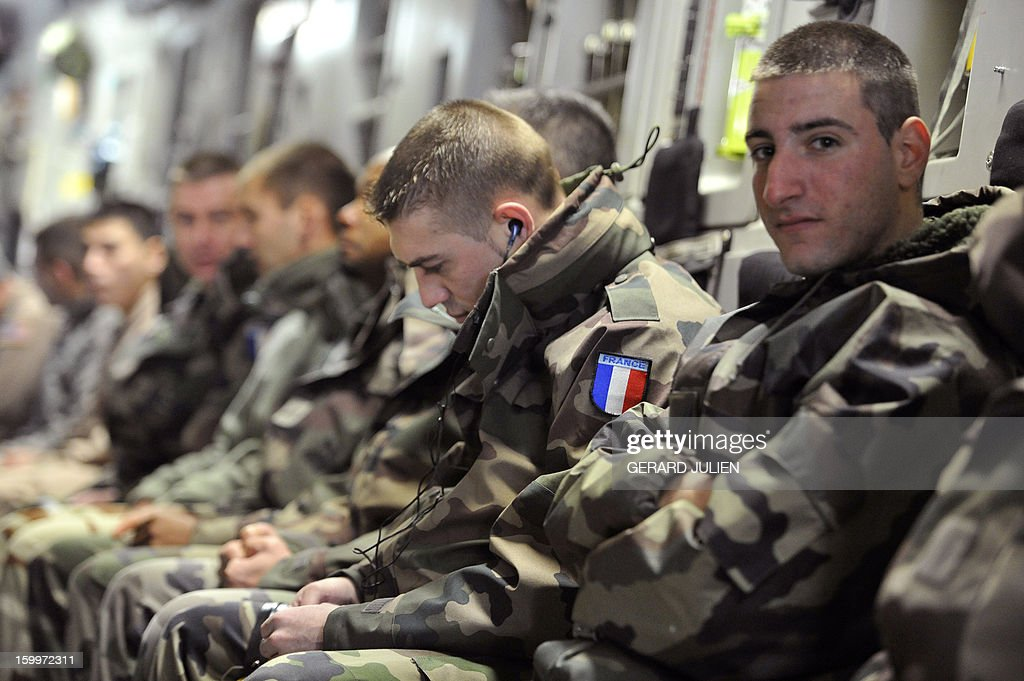French soldiers sit aboard a C17 aircraft of the US Airforce carriying French armoured vehicles at the Istres military airport (BA 125) on January 24, 2012 in Istres, southern France, prior to take off and heading toward Mali as part of the 'Serval' operation. AFP PHOTO / GERARD JULIEN